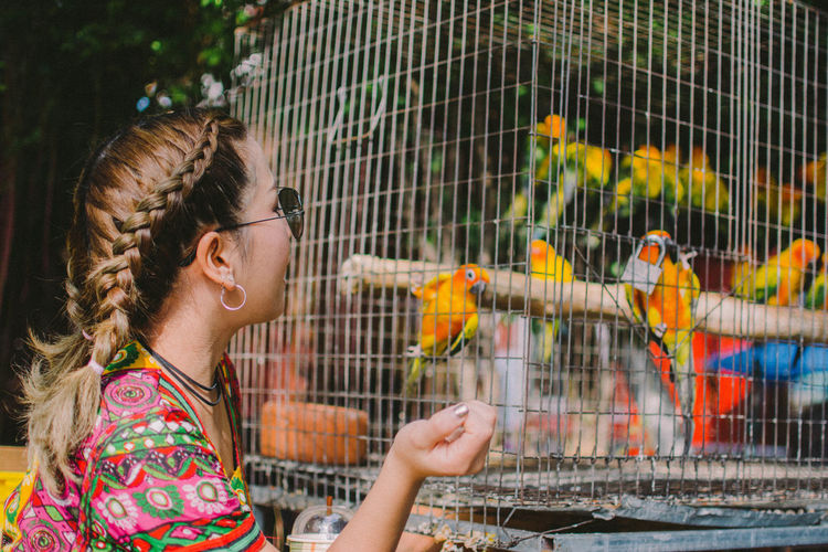 Woman looking at birds in cage