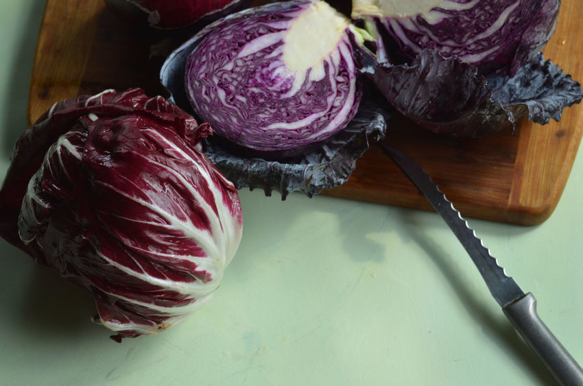 radicchio, knife, cut red cabbage on bamboo cutting board on light green surface Cabbage Close-up Cut Cutting Cutting Board Cutting Boards Focus On Foreground Food Freshness Green Indulgence Knife No People Pink Color Preparation  Preparing Food Radicchio Ready-to-eat Red Cabbage Serving Size Still Life Temptation