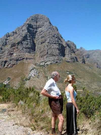 Side View Of Grandfather And Granddaughter Standing On Rock Against Clear Sky