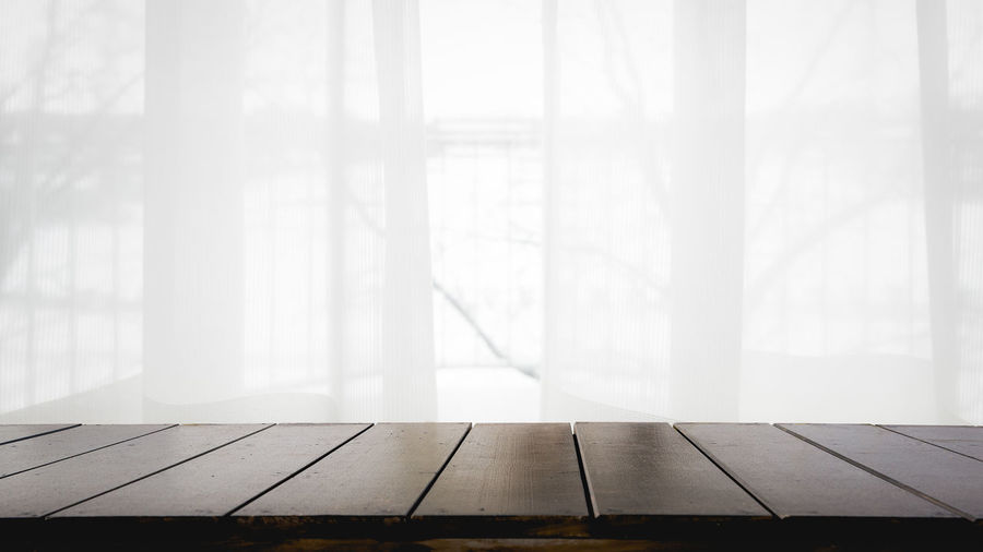 Empty table by window in foggy weather