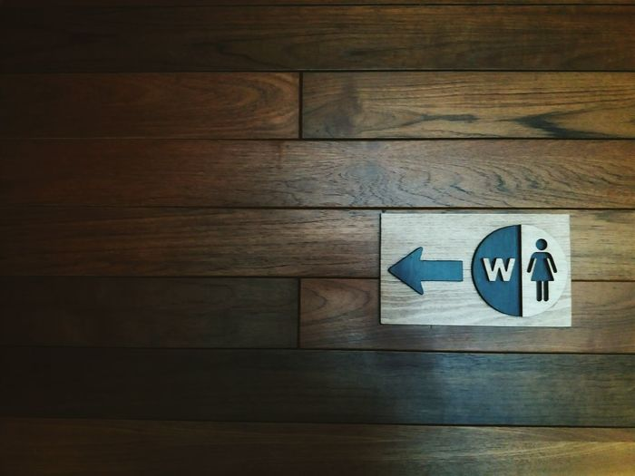 The way go to women toillet or rest roomClose-up Wood - Material Sign Logo Woman Wooden Floor Wooden Background Toilet Sign Copy Space Entrance Way Turn Left Indoors  Icon Restroom Pee Design