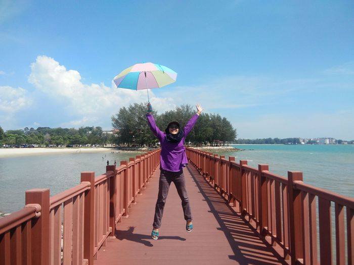 Full Length Of Woman With Umbrella Jumping On Bridge Against Sky
