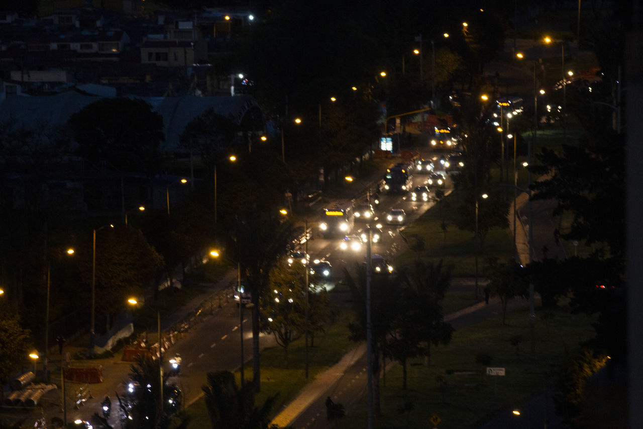 VIEW OF ILLUMINATED CITY STREET AT NIGHT