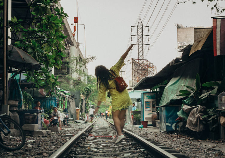 The Traveler - 2018 EyeEm Awards Architecture Building Exterior Built Structure Casual Clothing Day Full Length Lifestyles Mode Of Transportation Nature Outdoors People Public Transportation Rail Transportation Railroad Track Real People Rear View Standing Track Transportation Women