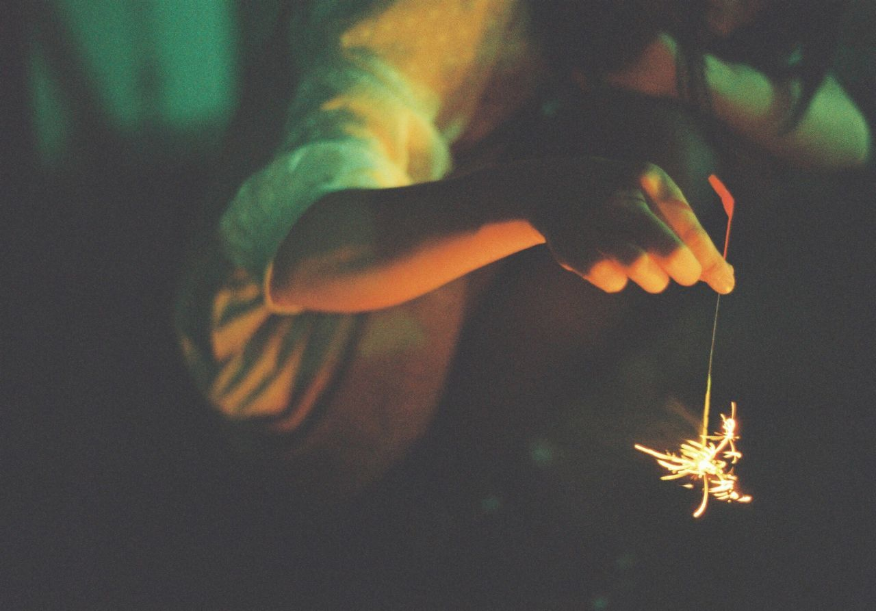 Low section of woman holding sparkler