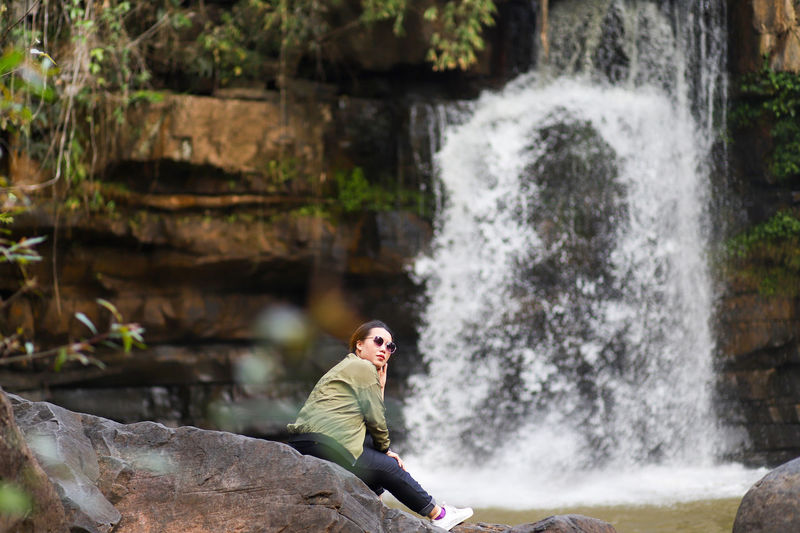 Side view of woman wearing sunglasses against waterfall