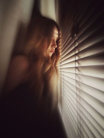 Woman Looking Through Blinds