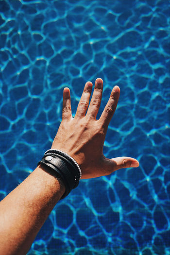 Cropped hand of man over swimming pool
