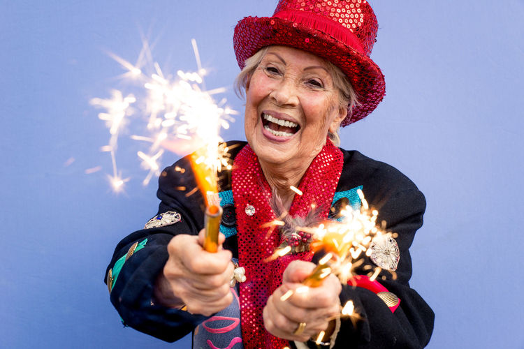 Portrait of happy senior woman wearing hat holding sparklers against blue background