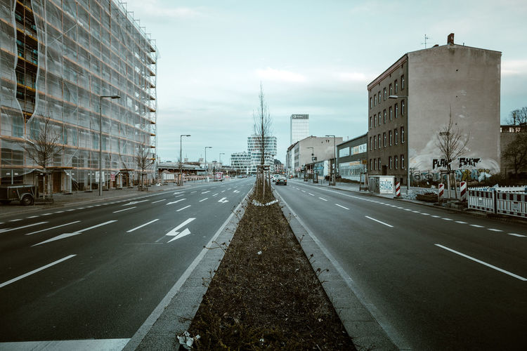Road by cityscape against sky