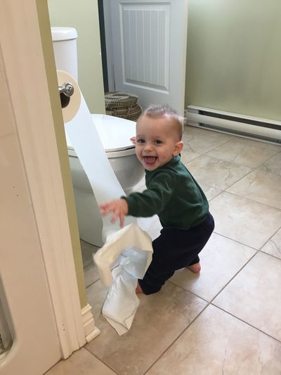Full length of cute baby boy standing in toilet
