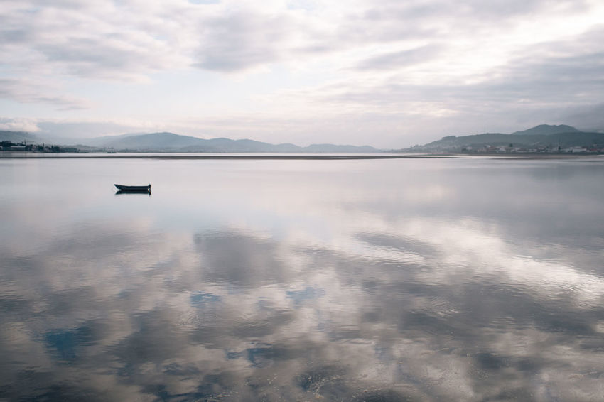 take a look at the spanish side Beauty In Nature Boat Calm Cloud Cloud - Sky Cloudy Day Fishing Boat Hikinggalicia Idyllic Lake Mountain Mountain Range Nature No People Non-urban Scene Outdoors Reflection Remote Scenics Tranquil Scene Tranquility Water Weather Lost In The Landscape