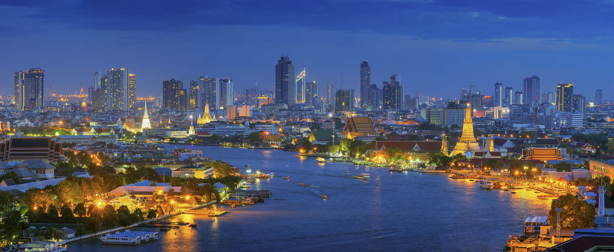 Panorama Views of Bangkok and the Chao Phraya River Wat Arun curve. Against a backdrop of high-rise buildings at dusk. Bangkok City Panorama Night Thailand View River Skyline Downtown Tower Dubai Building Skyscraper Architecture Modern Hotel Travel Sky Nighttime ASIA Blue Bridge Light Water Reflection