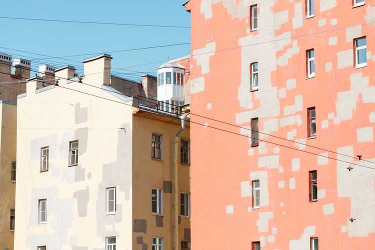 Architecture Built Structure Building Exterior Window Building Residential District Day No People Low Angle View City Nature Outdoors Cable Sunlight Sky Clear Sky Wall - Building Feature Orange Color Blue Wall Apartment