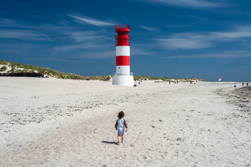 Rear view of girl walking at beach against sky