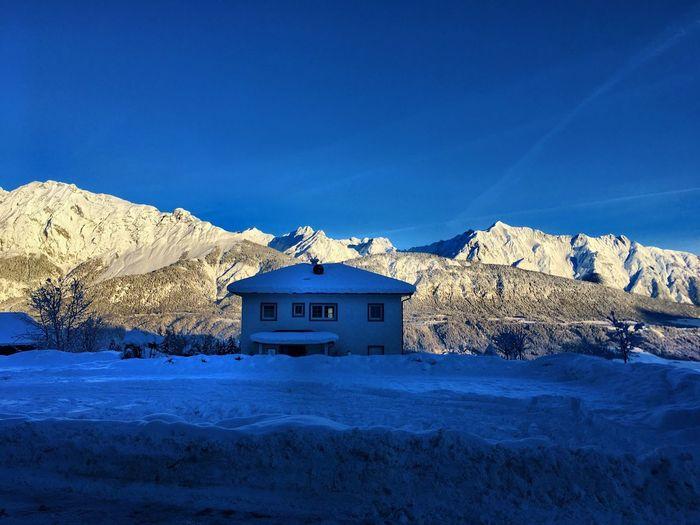 Houses on snowcapped mountain against blue sky