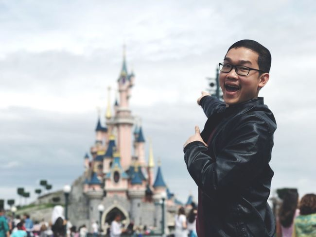 EyeEm Selects Disneyland Real People Lifestyles Smiling Happiness Leisure Activity Incidental People Young Adult Focus On Foreground Sky Tourism One Person Architecture Toothy Smile Casual Clothing Looking At Camera Outdoors Young Women Cloud - Sky Travel Destinations Day
