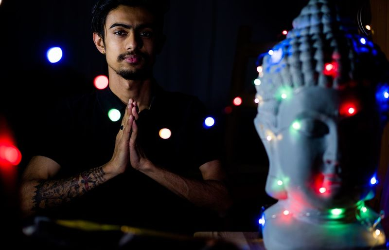 Portrait of young man praying against buddha statue at night