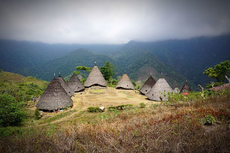 High angle view of traditional houses on hill against mountains during foggy weather