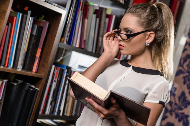 Woman holding book while standing at library