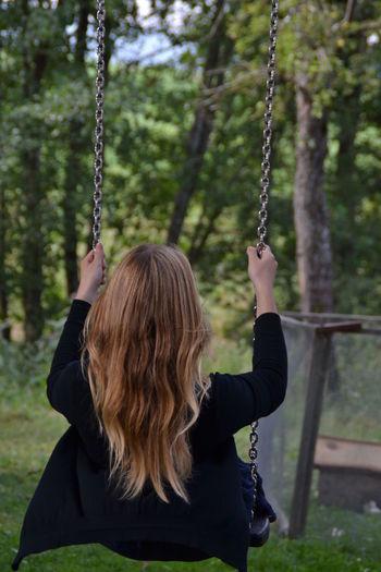 Rear view of woman on swing