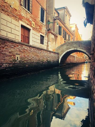 Bridge over canal by buildings