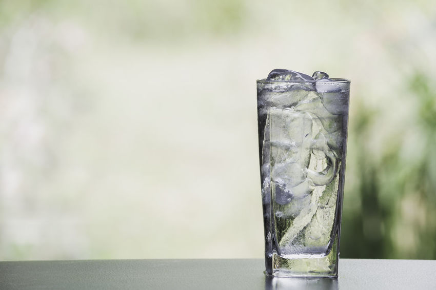 Ice cube and water in the glass on table with nature background Focus On Foreground Glass Drinking Glass Close-up Cold Temperature Ice Cube No People Household Equipment Drink Food And Drink Frozen Transparent Refreshment Day Glass - Material Ice Outdoors Water Freshness Tonic Water Melting