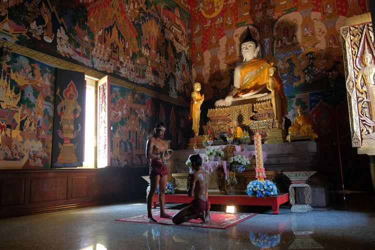 Shirtless men praying in buddhist temple