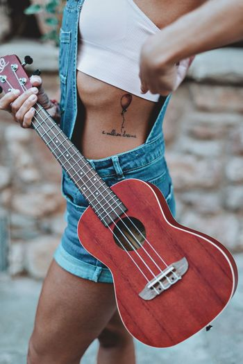 Midsection of woman showing tattoo while holding guitar