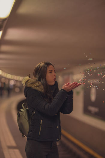 Young Woman Blowing Confetti While Standing Against Train At Subway Station