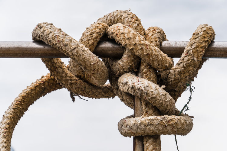 Low Angle View Of Rope Tied On Metal Rod Against Clear Sky