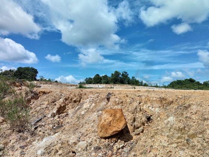 Rocks on field against sky