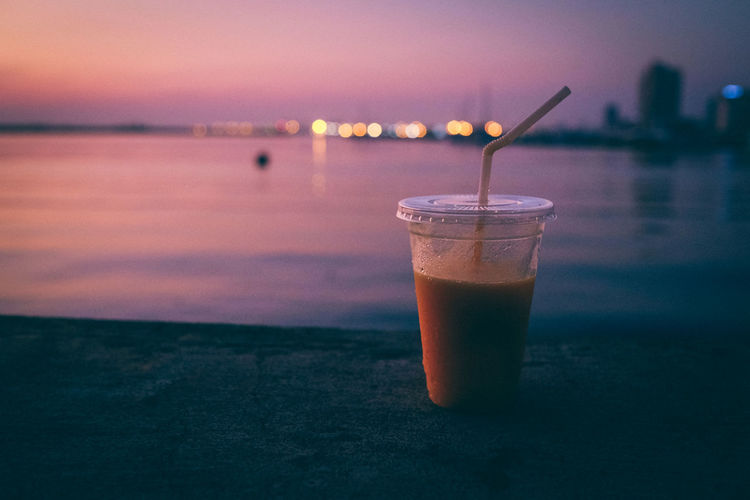 Close-up of drink against sea during sunset