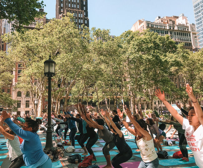 Yoga Group Of People Real People Crowd Architecture Building Exterior Built Structure Tree Large Group Of People Plant Human Arm Men Arms Raised Lifestyles City Day Nature Celebration Women Outdoors Human Limb Yoga New York City Outdoor Yoga Yoga Class