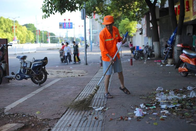Full length of worker sweeping footpath