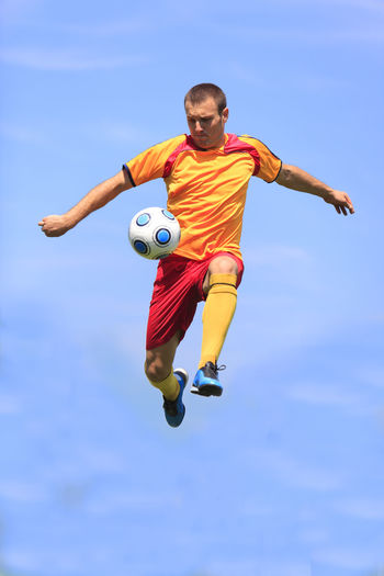 Man playing soccer against blue sky