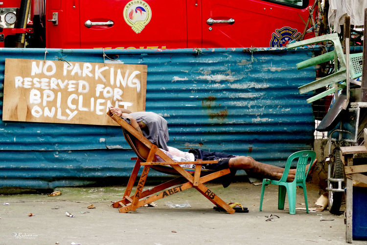 No Parking Street Life Blue And Red Corrugated Iron Day Man Asleep Outside On A Chair Outdoors Sleeping