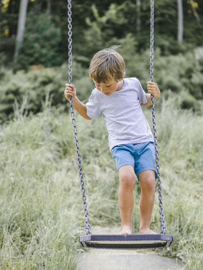Full length of boy on swing at playground
