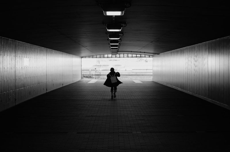 Rear View Of Silhouette Person Walking In Tunnel