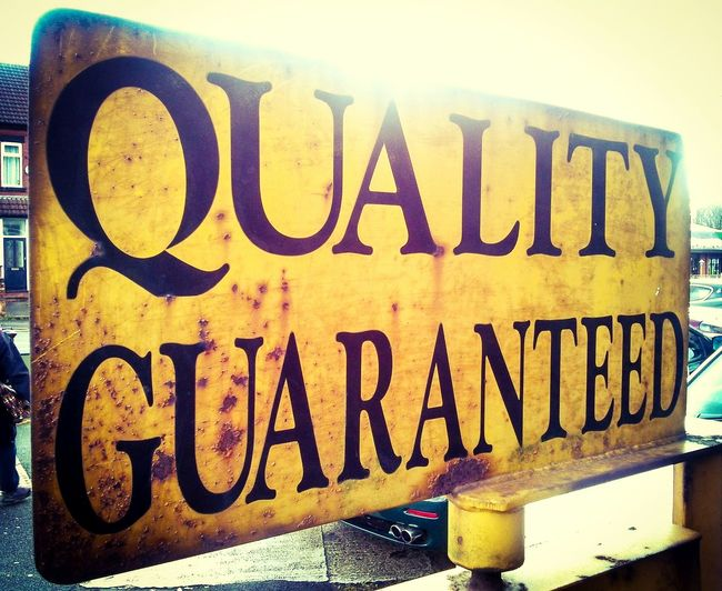 """Quality Guarantee.. that you get with The Big Town. Taken in """"lovely"""" Chorlton. Sign Quality Reassurance Advertisement Yellow Metal Sign Manchester"""
