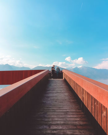 Orange Perspective Bridge Bridgesaroundtheworld Cloud - Sky Footbridge Leisure Activity Lifestyles Nature One Point Perspective Outdoors Rear View Sky The Way Forward Togetherness Two People