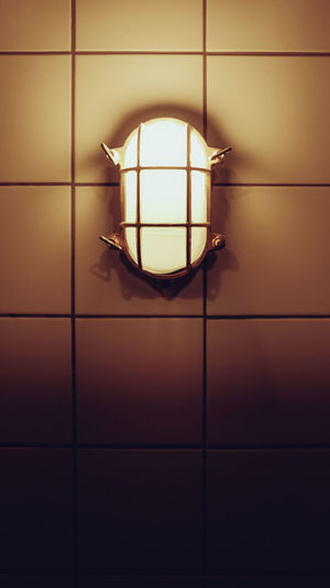 Close-up of illuminated lamp hanging on tiled floor