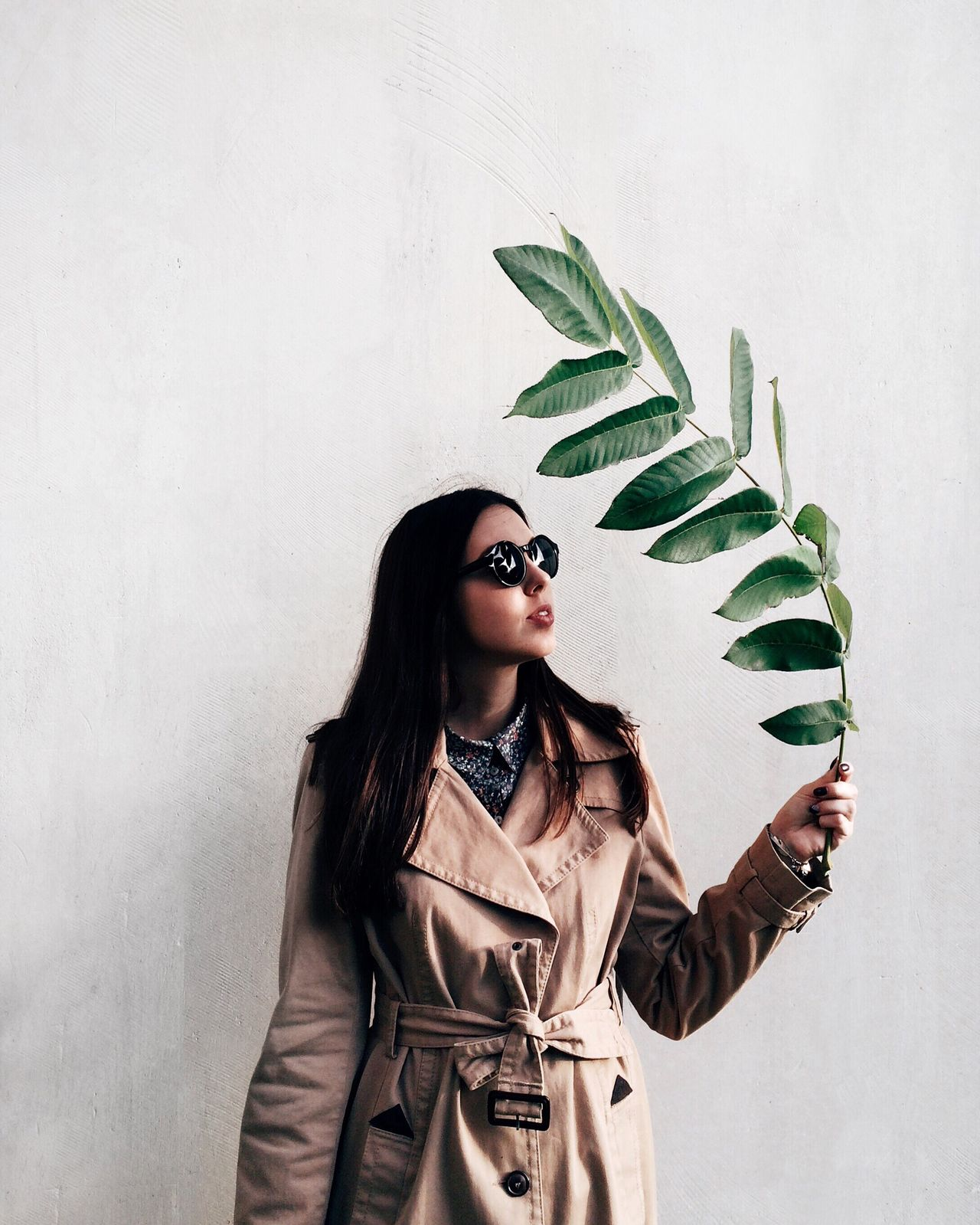 Woman holding twig with green leaves while standing against wall