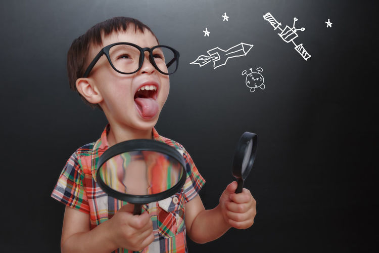 Boy Screaming While Holding Magnifying Glasses Against Blackboard