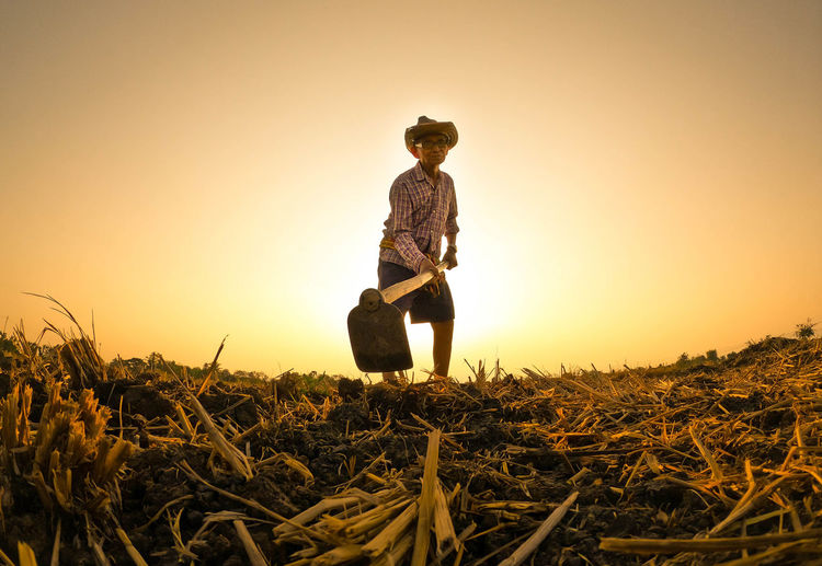 Man working on field against clear sky during sunset