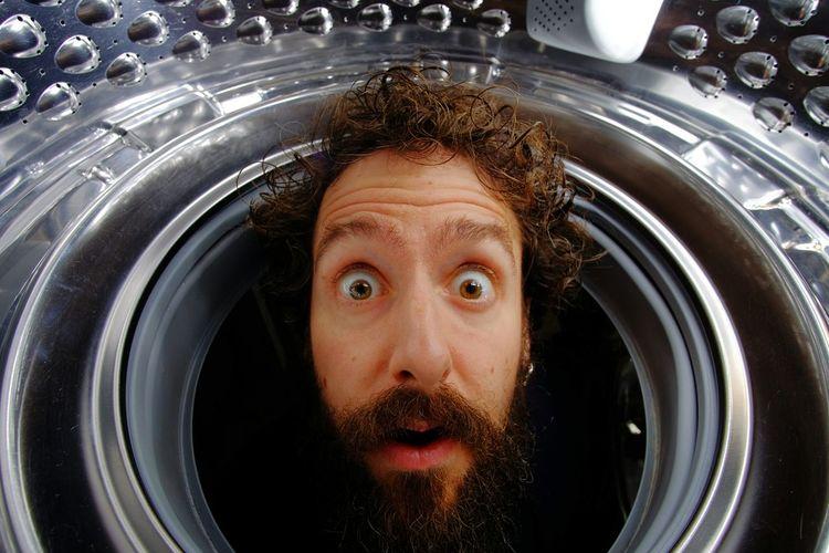 Close-up portrait of shocked man in washing machine