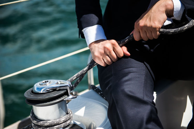 Midsection of businessman holding rope while sitting on boat