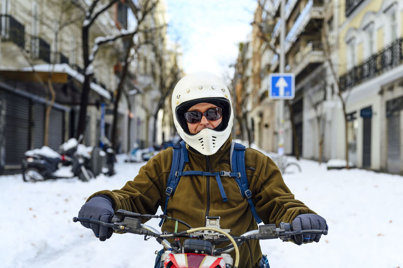 Portrait of man riding bicycle on snow