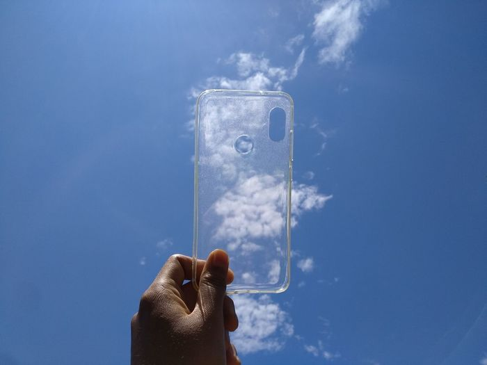 Person holding phone case against blue sky