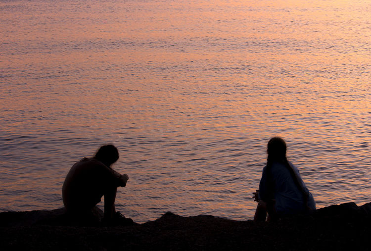 Rear view of couple silhouettes sitting on land against sea during sunset or sunrise